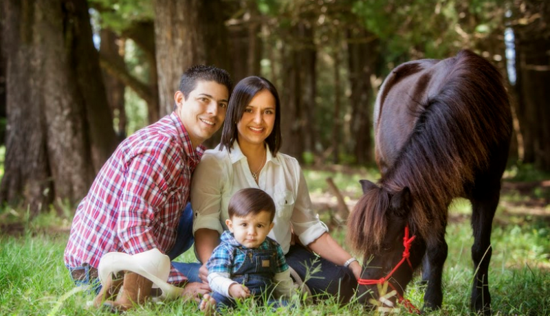 family portrait, mom and dad with baby and a pony