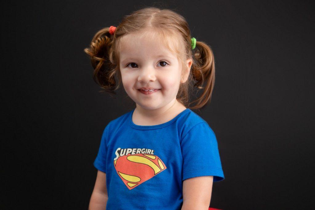 smiling girl on supergirl shirt