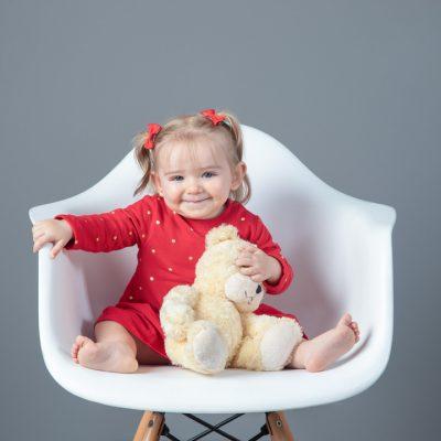 Sesion en estudio niña vestido rojo en silla blanca