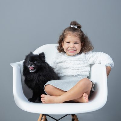 Sesion mascotas en estudio niña con perro negro en silla blanca